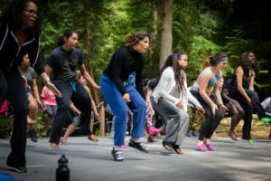 A large group of students in the woods performing a coordinated dance at Partners for Youth's Power of Hope summer camp