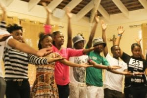 A group of students making a rhythm stand mid clap with one arm straight out in front of their body, and one raised straight above their head.