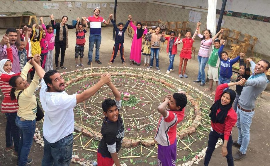Mentors and youth in Egypt joining hands around a newly completed art project they completed together.