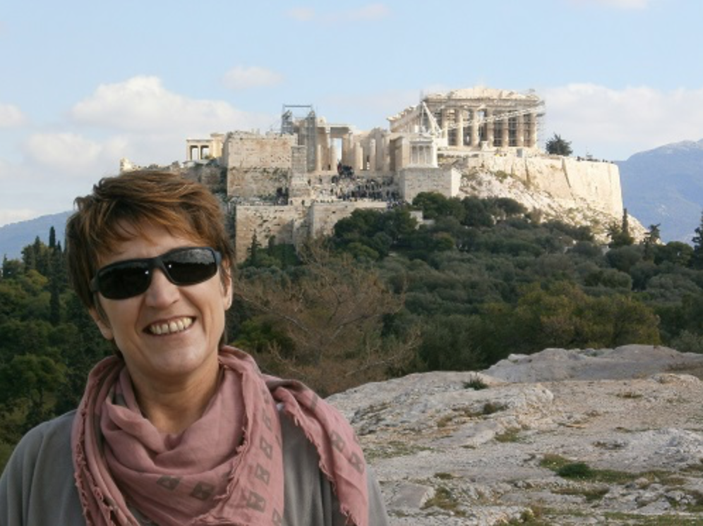 Creative Classroom participant Kleopatra Kalogerakou stands on a ridge, an ancient greek temple stands behind her off in the distance